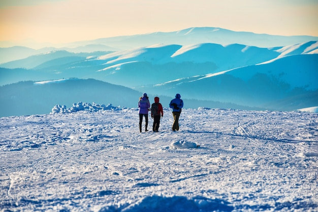 Mensen lopen bij zonsondergang in de bergen van de winter bedekt met sneeuw