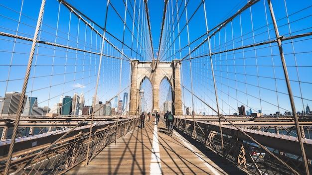Mensen lopen en fietsen op de brooklyn bridge in new york city