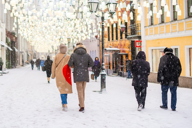 Mensen lopen in de straten van de stad onder snowall b