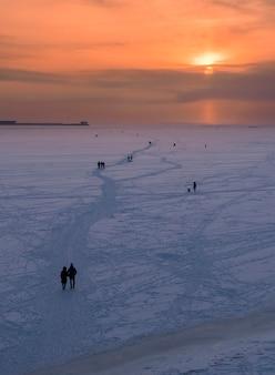Mensen lopen langs de bevroren oostzee, de golf van finland in de winter bij zonsondergang in st. petersburg, rusland