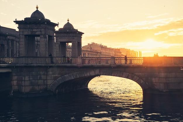 Mensen lopen langs de brug van lomonosov bij zonsondergang, st. petersburg