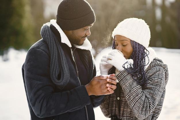 Mensen lopen naar buiten. winter dag. afrikaans echtpaar met koffie.
