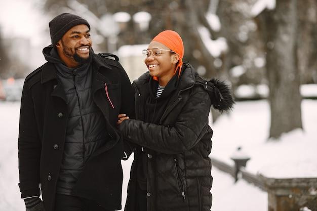 Mensen lopen naar buiten. winter dag. afrikaans echtpaar.