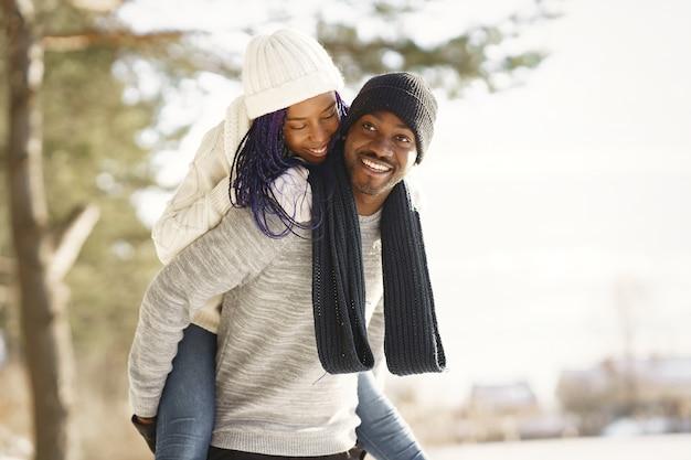 Mensen lopen naar buiten. winter dag. afrikaans echtpaar