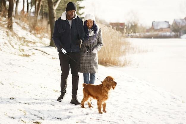 Mensen lopen naar buiten. winter dag. afrikaanse echtpaar met hond.