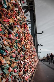 Mensen lopen op de stoep met hangsloten in verschillende kleuren op een hek