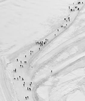 Mensen lopen op sneeuwveld overdag