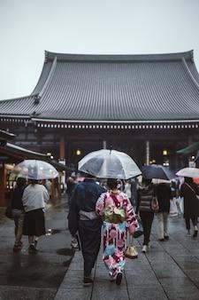Mensen lopen op straat terwijl ze paraplu's vasthouden die naar de pagode gaan