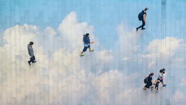 Mensen lopen verder over het voetgangersbeton met hardscape weerspiegelen wolk.
