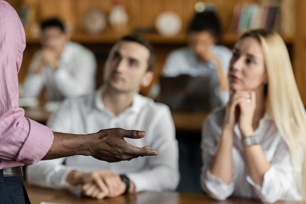 Mensen luisteren en kijken naar een man die een presentatie houdt op het werk