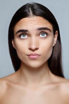 Mensen, luxe en mode, emoties concept - portret van een jonge vrouw met geschokte gezichtsuitdrukking