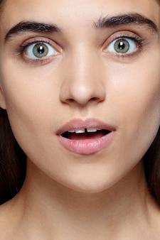 Mensen, luxe en mode, emoties concept - portret van jonge vrouw met geschokte gezichtsuitdrukking, close-up van mooie brunette vrouw met mooie ogen en kloof tussen de tanden