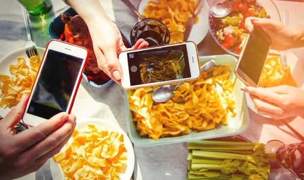 Mensen maken een beeld van voedsel voor sociaal netwerk voordat ze kip en spaghetti gaan eten. boven weergave