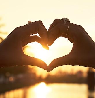 Mensen maken een hart met handen bij zonsondergang