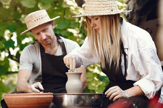 Mensen maken een vaas met klei