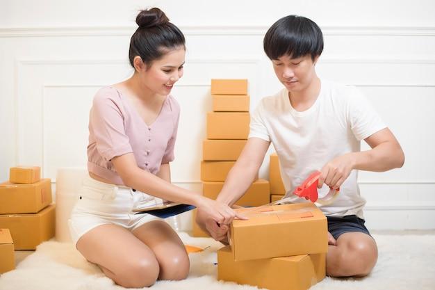 Mensen maken producten met kartonnen dozen klaar voor verzending