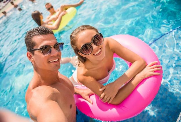 Mensen maken selfie terwijl ze plezier hebben in het zwembad.