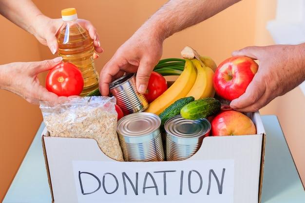 Mensen maken voedsel uit een donatiebox.