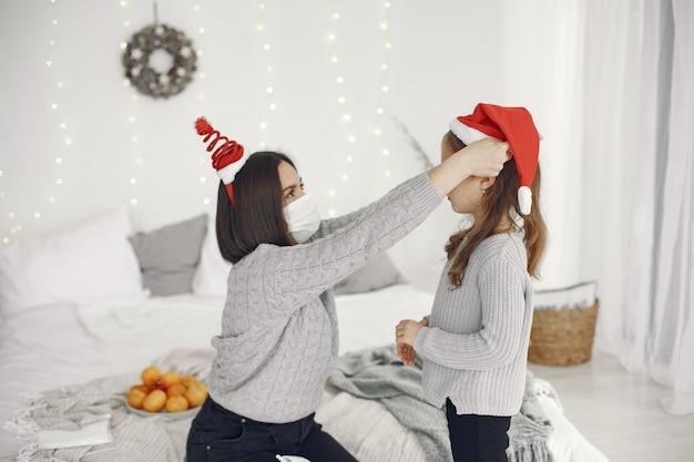 Mensen maken zich klaar voor kerstmis. coronavirus-thema. moeder speelt met haar dochter. kind in een grijze sweater.