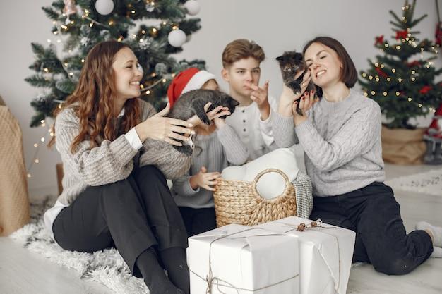 Mensen maken zich klaar voor kerstmis. mensen die bij de kerstboom zitten.
