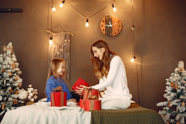Mensen maken zich klaar voor kerstmis. moeder speelt met haar dochter. familie rust in een feestelijke kamer. kind in een blauwe trui.