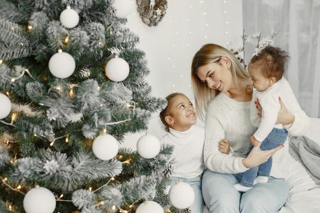 Mensen maken zich klaar voor kerstmis. moeder speelt met haar dochters. familie rust in een feestelijke kamer. kind in een sweatertrui.