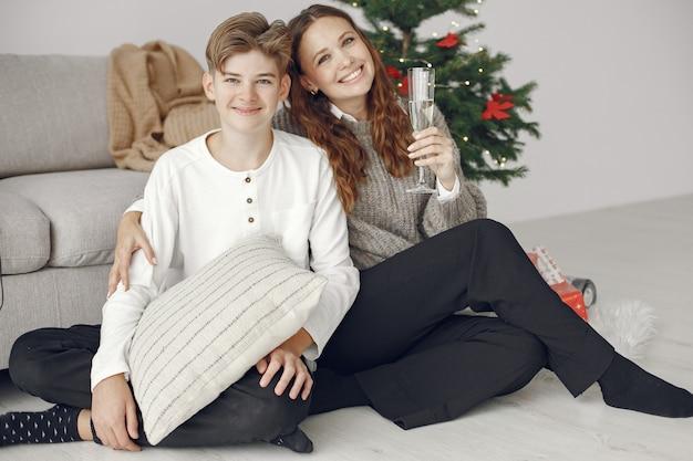 Mensen maken zich klaar voor kerstmis. moeder stond met haar zoon. familie rust in een feestelijke kamer. mensen met champagne en wonderkaarsen.