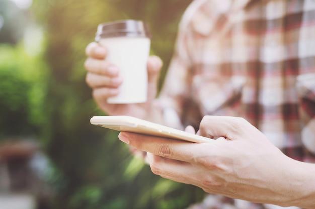 Mensen man hand met papieren kopje afhaalmaaltijden koffie drinken op natuurlijk ochtendzon.