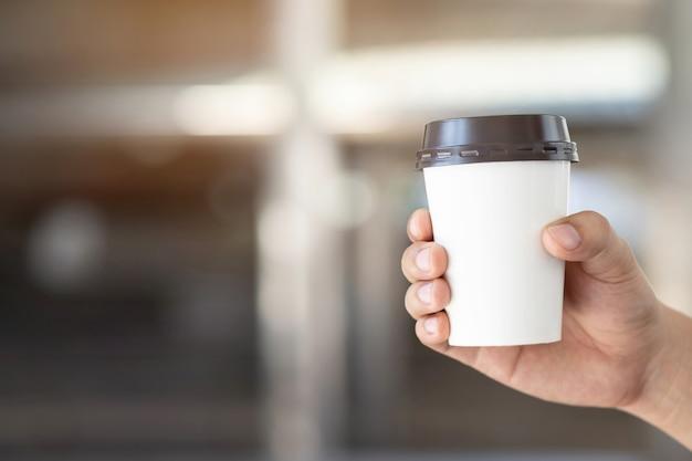 Mensen man hand met papieren kopje afhaalmaaltijden koffie drinken op natuurlijke ochtendzon zittend in openbaar park.