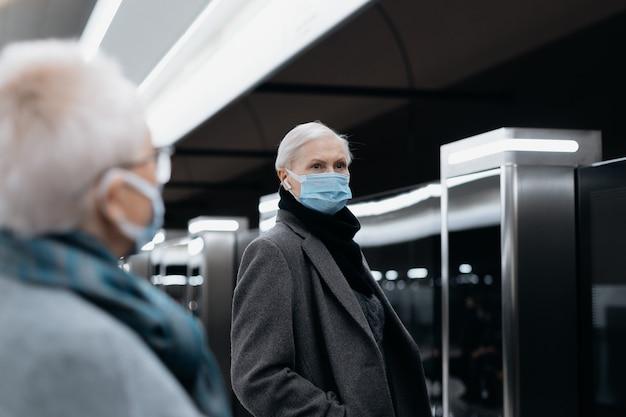 Mensen met beschermende maskers die op het metroperron staan