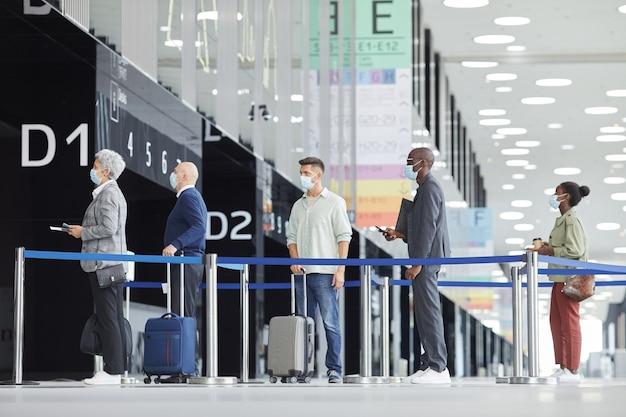 Mensen met beschermende maskers staan met koffers achter elkaar op de luchthaven