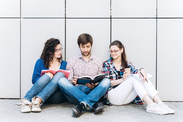 Mensen met boeken en gadgets zitten op de vloer bij de muur. onderwijs social media concept.