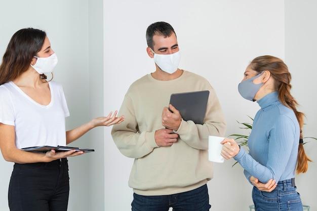 Mensen met een gemiddeld shot die op het werk praten