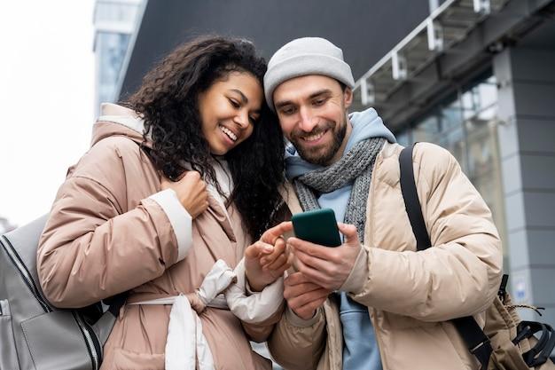 Mensen met een gemiddelde shot die naar de telefoon kijken
