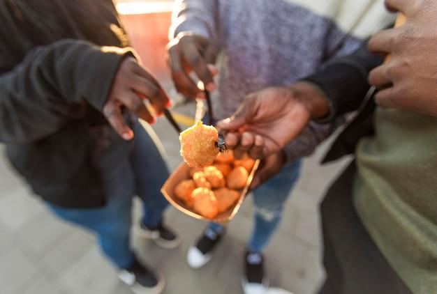Mensen met een hoge hoek eten kipnuggets uit afhaalverpakkingen