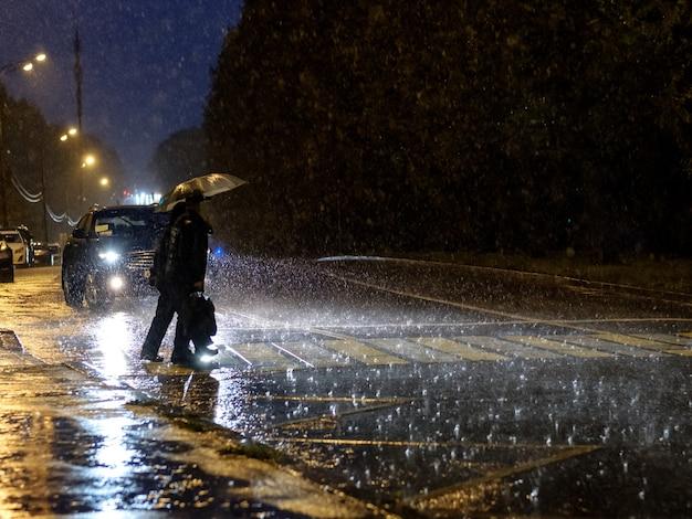 Mensen met een paraplu in de regen lopen 's nachts langs het zebrapad