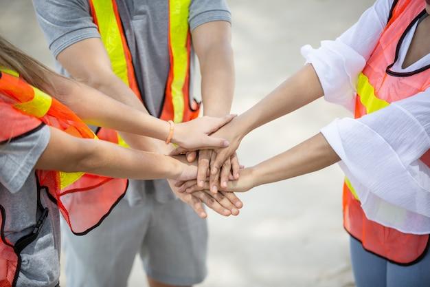 Mensen met gebundelde handen als team