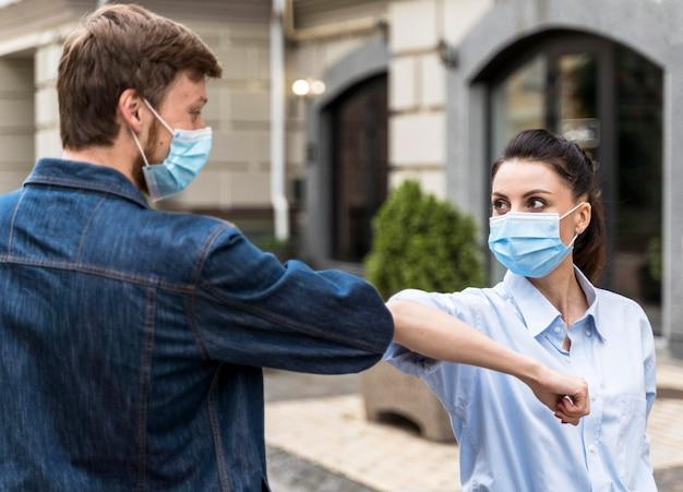 Mensen met gezichtsmaskers die met hun elleboog buiten stoten