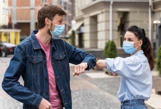 Mensen met gezichtsmaskers stoten elleboog