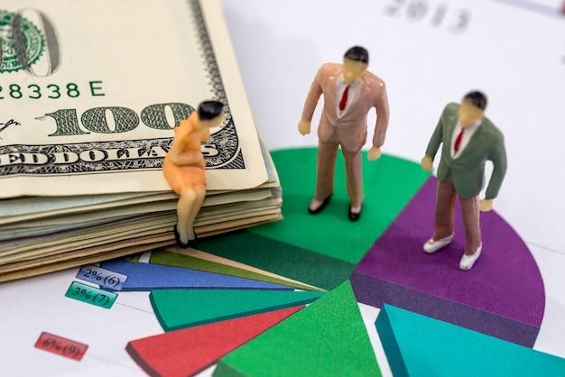Mensen met klein speelgoed bespreken het schema en de dollars