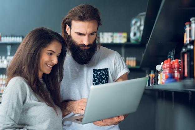 Mensen met laptop in een elektronische sigarettenwinkel.