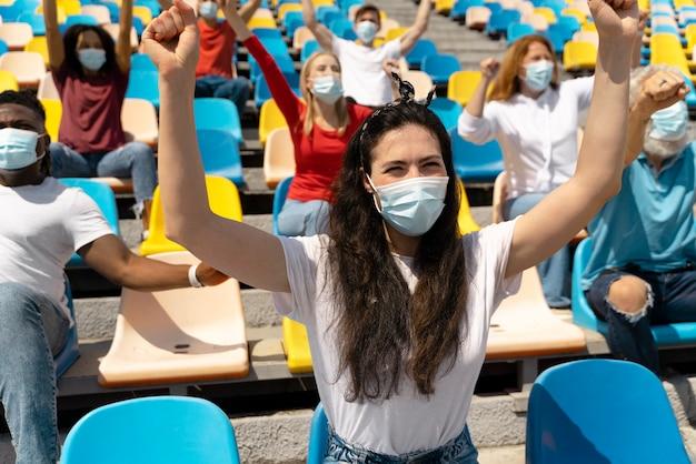 Mensen met medische maskers die naar een spel kijken