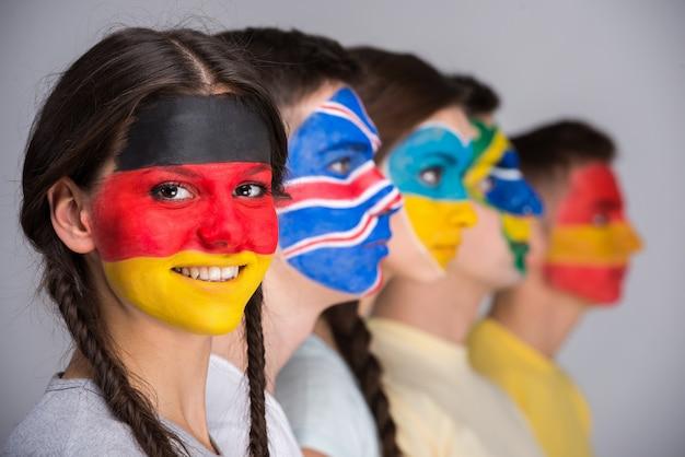Mensen met nationale vlaggen geschilderd op de gezichten.