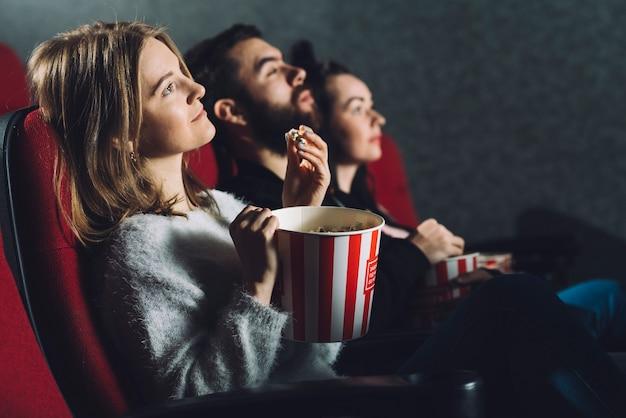 Mensen met popcorn die van film genieten