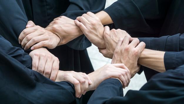 Mensen met zwarte toga komen hand in cirkellus bij elkaar