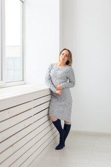 Mensen, mode en beauty concept - jonge vrouw in wollen jurk poseren in de buurt van vensterbank