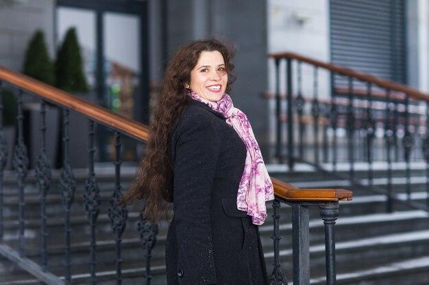 Mensen, mode en seizoen concept - stijlvolle jongedame in vacht poseren op trappen in winterdag