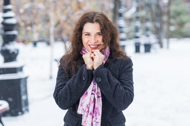 Mensen, mode en seizoenconcept - het mooie gelukkige glimlachende jonge vrouw stellen op besneeuwde winter