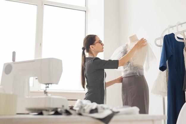 Mensen, mode en showroom concept - jonge modeontwerper in haar showroom.