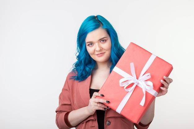 Mensen, mode en vakantieconcept - mooi meisje met blauw haar dat zich met giftdoos op witte achtergrond bevindt.